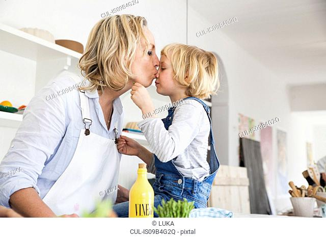 Mature woman kissing daughter at kitchen table