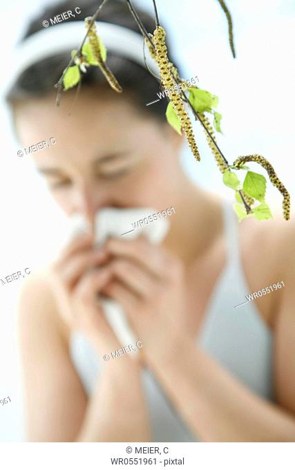 a branch with leaves of a birch tree - in the background blurred a young woman sneezing and giving her nose a blow