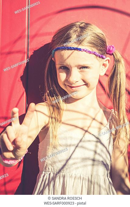 Portrait of smiling little girl in summer showing victory sign