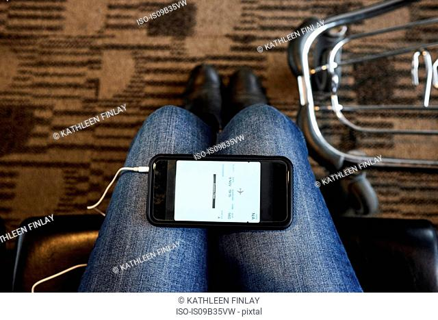 Personal perspective of smartphone on woman's knees in airport lounge