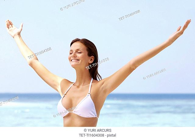 Young woman in bikini, arms outstretched