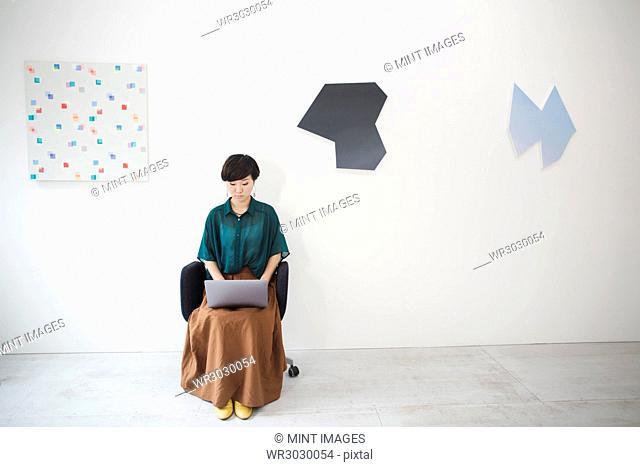Woman with short black hair wearing green shirt sitting in art gallery, typing on laptop computer