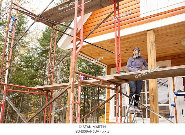 Mid adult woman standing on scaffolding stepladder outside house