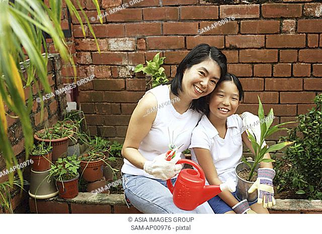 Mother and daughter, sitting in garden, looking at camera