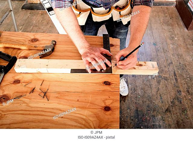 Cropped view of carpenter marking timber using set square
