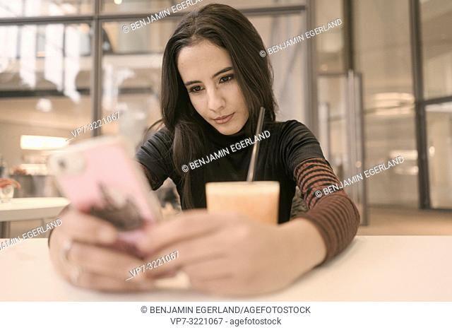 portrait of focused woman using phone while taking a break with juice glass at table in café, in Munich, Germany