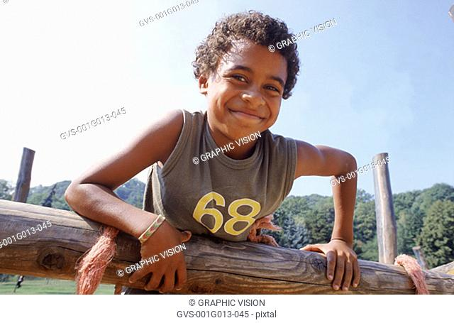 Young boy leaning on a wooden fence