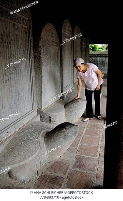 Literature Temple in Hanoi. Pregnant woman feeling the head of the stone turtles wishing for luck. In the steallae there have been carved the names and dids of...