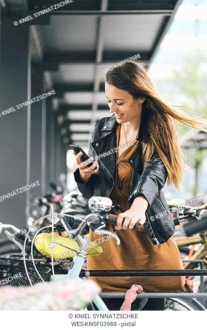 Smiling young woman with bicycle using cell phone in the city