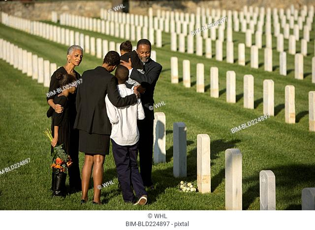 Multi-generation Black family hugging in military cemetery