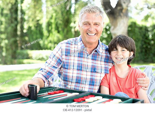 Grandfather and grandson playing backgammon on patio