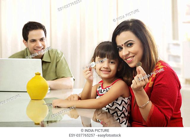 Mother and daughter counting piggy bank coins and father working on laptop