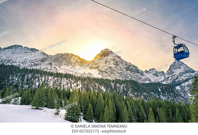 Winter scenery with the sun hiding behind the Alps mountains, covered by fir forests, and a cable car crossing them. Image captured in Ehrwald, Austria