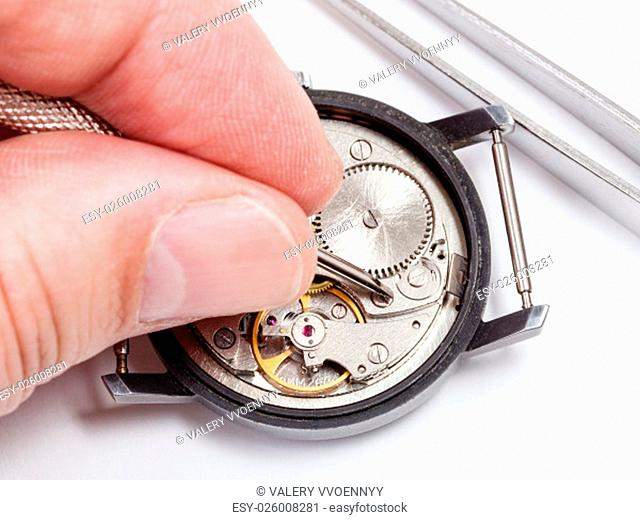 adjusting old mechanic wristwatch - watchmaker repairs old watch close up