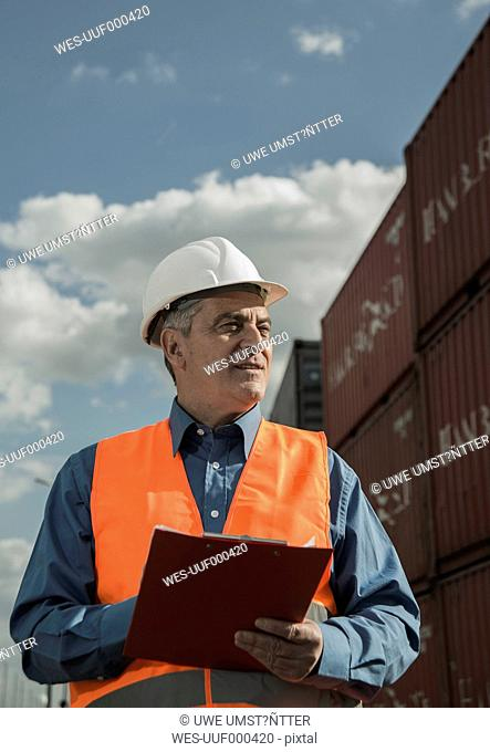 Man with clipboard wearing reflective vest at container port