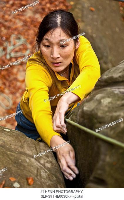 Woman rock climbing on boulder