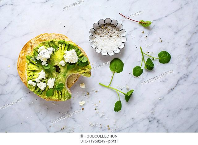 A bagel with avocado, ricotta, watercress, salt and pepper