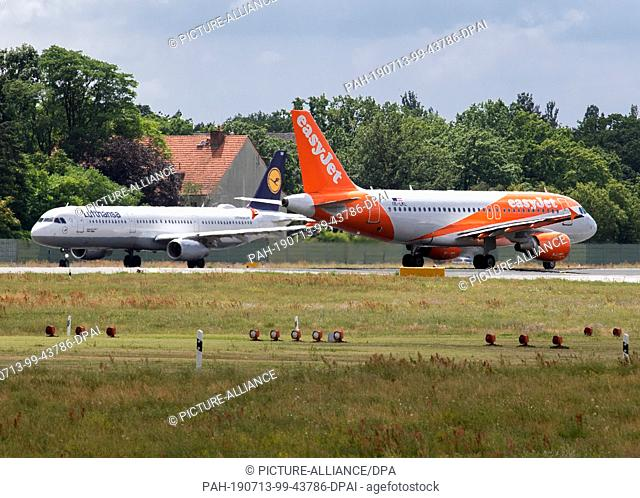 13 July 2019, Berlin: Aircraft of the airlines easyJet and Lufthansa are waiting at Tegel Airport for take-off clearance