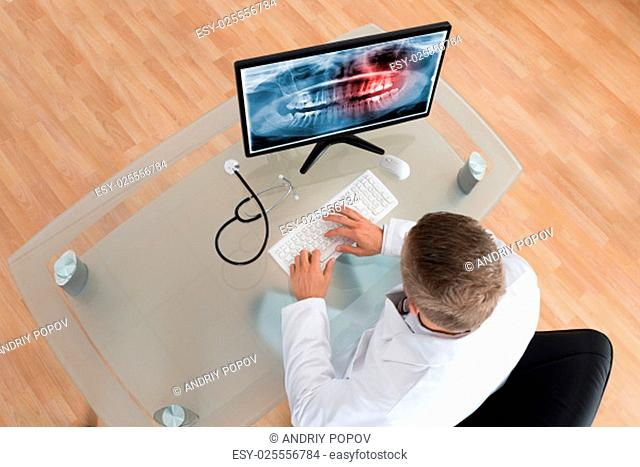 Young Doctor Examining Teeth X-ray On Computer At Desk