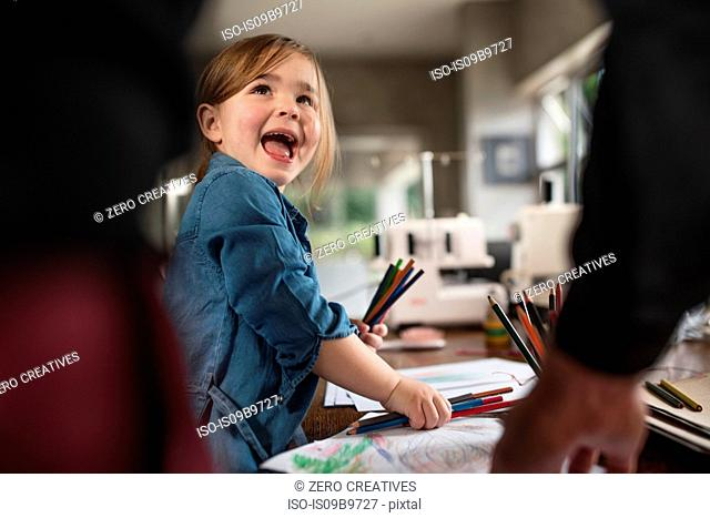 Girl and father selecting coloured pencils for drawing at table
