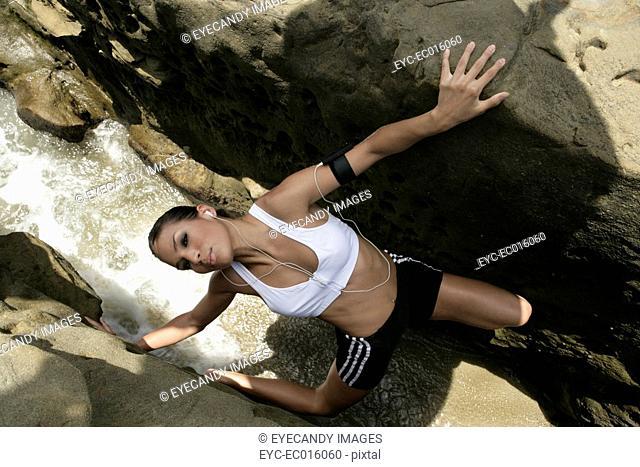 View of a woman climbing rocks
