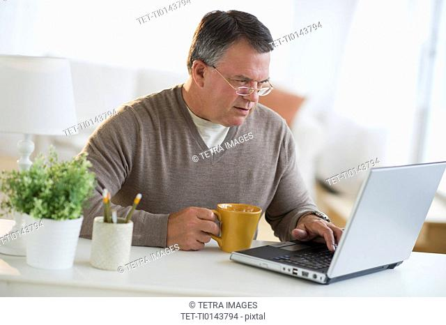 USA, New Jersey, Jersey City, Man using laptop, holding drink in living room