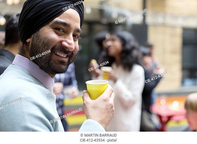 Portrait smiling man in turban drinking, enjoying party