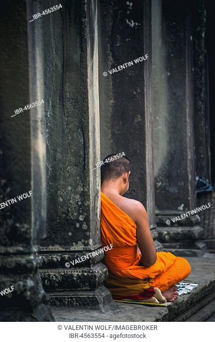 Buddhist monk meditates in colonnade, temple complex of Angkor Wat, Angkor Archaeological Park, province of Siem Reap, Cambodia