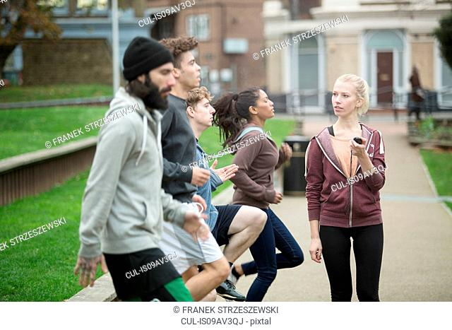 Group of adults exercising outdoors, young woman holding stopwatch