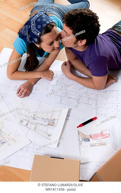 Young couple on the floor making plans for new home