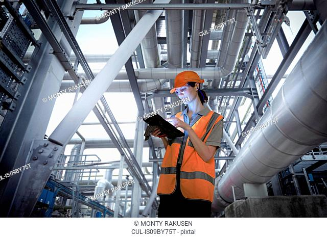 Composite image of female worker in storage plant using digital tablet