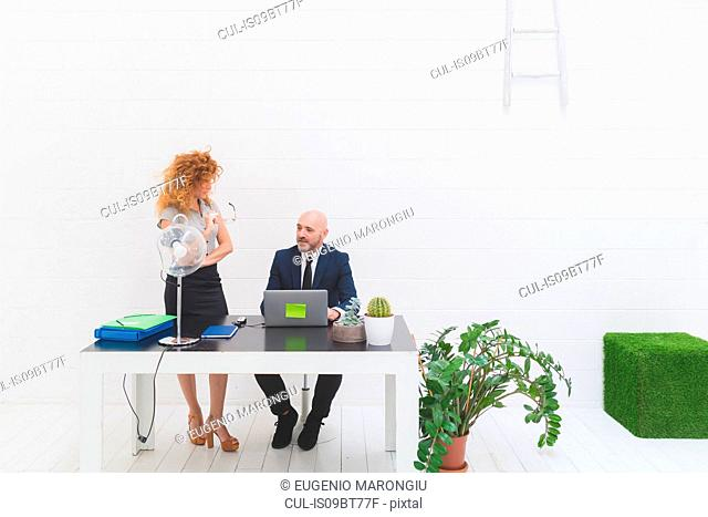 Businessman and woman having discussion in office