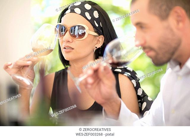 Man and woman examining red wine on a wine tasting session