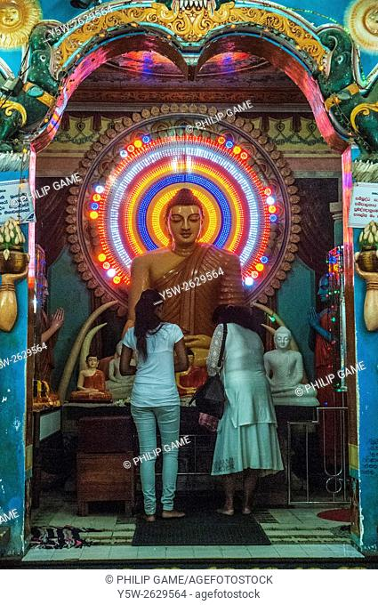 Women worshipping at a Buddhist shrine in the pilgrimage town of Kataragama, Sri Lanka
