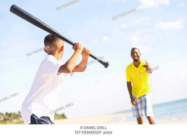 Father and son (10-11) playing baseball on beach