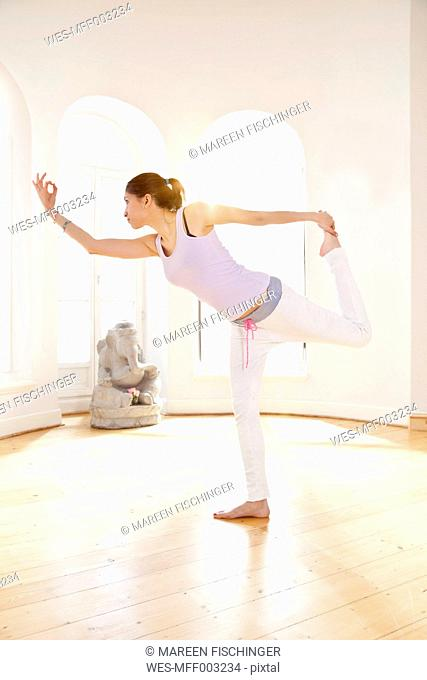 Woman in sunny yoga studio going into standard bow pose