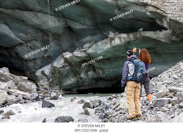 A woman takes a photograph of an ice cave with her cell phone while hiking to Gulkana Glacier with her husband; Alaska, United States of America