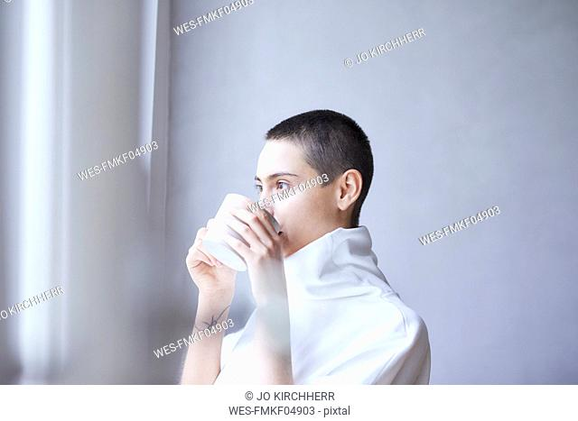 Portrait of short-haired young woman drinking from mug