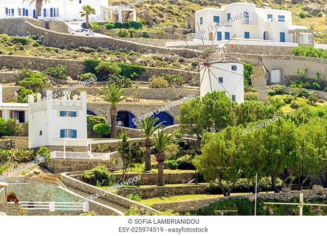 The cube whitewashed traditional houses and a windmill in Ornos, Mykonos, Greece. Very typical greek island architecture on a rocky hill