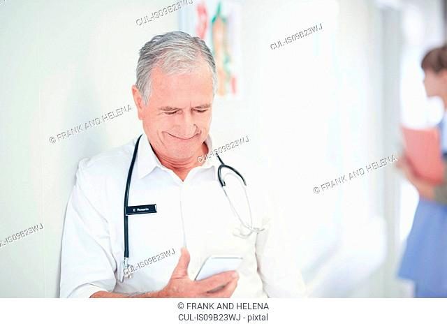 Senior male doctor reading smartphone message in hospital