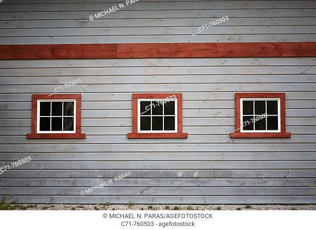 Three windows on side of a grey country barn