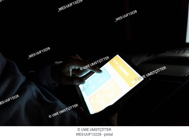 Businessman working on tablet at dark, close-up