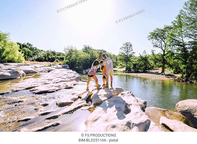 Friends posing for cell phone selfie on rocks near river