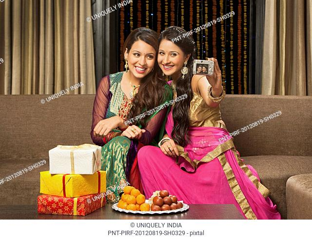 Female friends taking a picture of themselves with a camera on Diwali