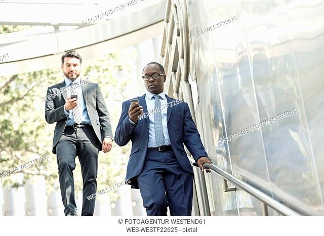 Two businessmen on the move looking at cell phones