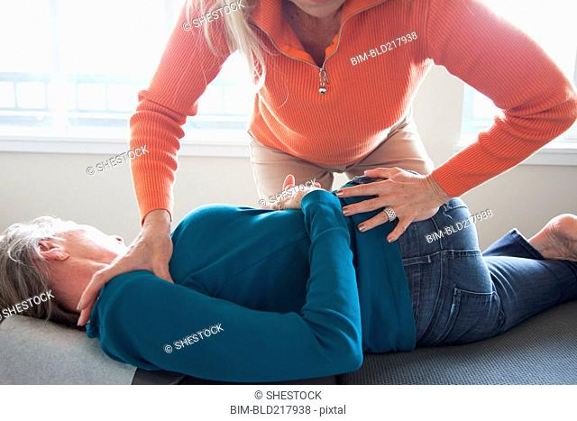 Caucasian chiropractor stretching back of client