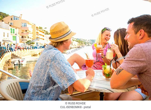 Two adult couples sharing cocktails at waterfront restaurant, Majorca, Spain