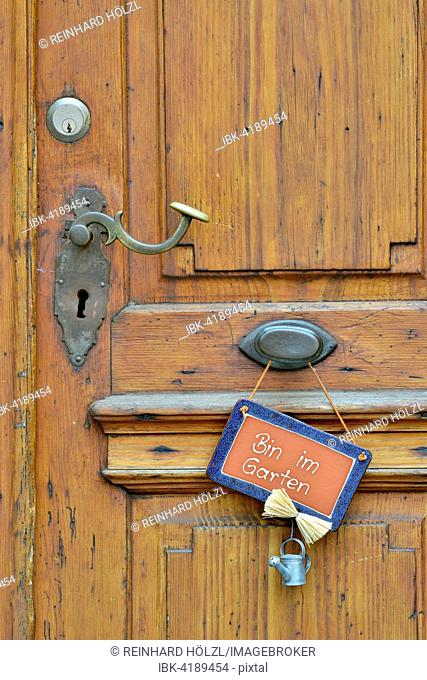 Wooden door with sign saying Bin im Garten, German for I'm in the garden, Baden-Württemberg, Deutschland
