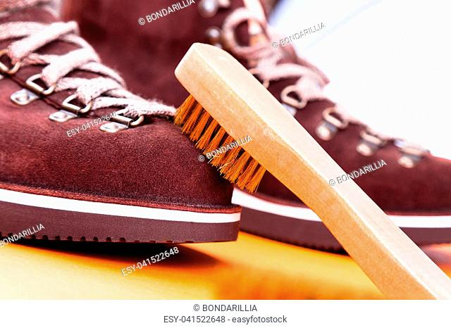 Brown man suede boots with brush. Macro. Clean shoes