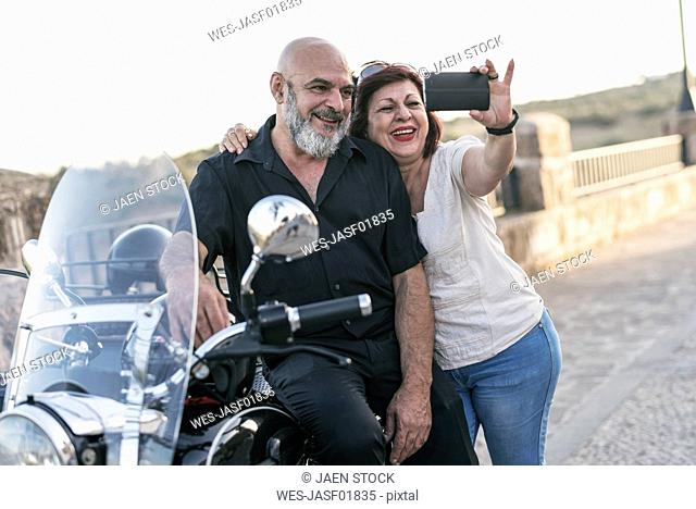 Spain, Jaen, mature couple with motorcycle with a sidecar taking a selfie